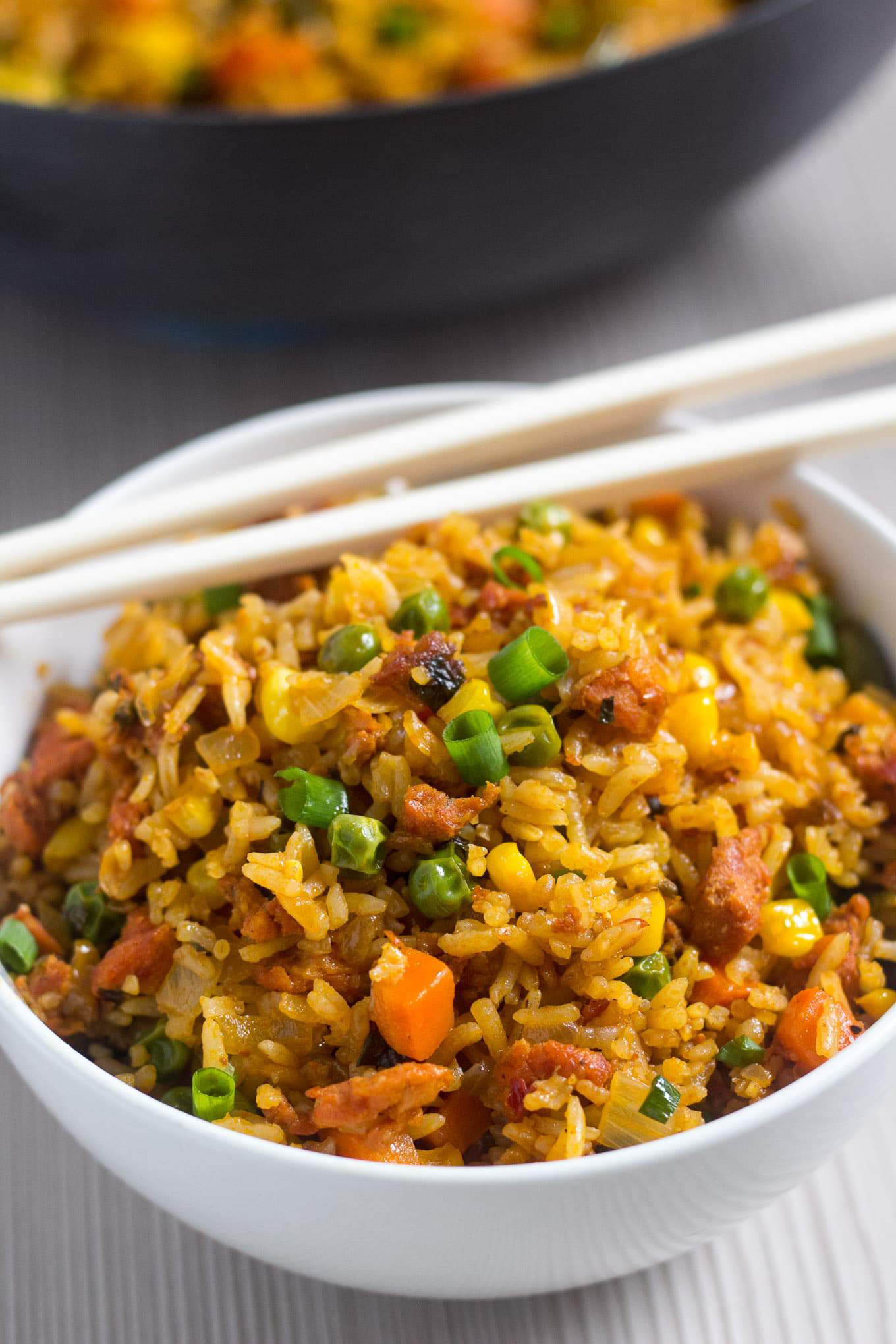 a bowl with fried rice and chop sticks on top.